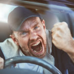A man driving loses his temper and shakes his fist, yelling, in a bout of road rage.